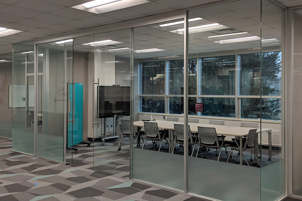 Image of the Digital Scholarship Lab's Project Room J. This room has a long rectangular table with chairs around it, a whiteboard, and a television screen.